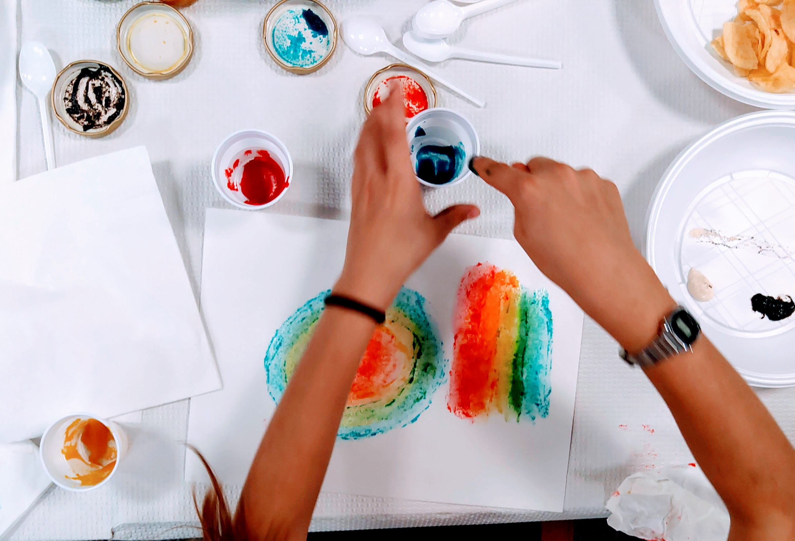 La bambina dipinge con marmellate colorate su tela di pane